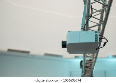 Multimedia projector mounted on metal rigg in exhibition hall or conference room