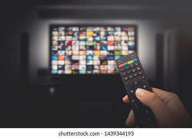 Multimedia video concept on TV set in dark room. Man watching TV with remote control in hand. - Shutterstock ID 1439344193