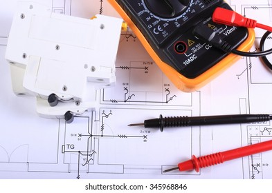 Multimeter with cables and electric fuse lying on construction drawing of house, electrical drawings and tools for engineer jobs
