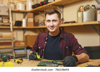 Multimeter for electrician. Caucasian young man in plaid shirt, black T-shirt digital electronic engineer repairing, soldering computer PC motherboard in workshop at wooden table with different tools