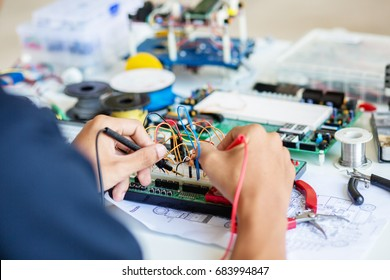 Multimeter examining a circuit board.Young energetic male tech or engineer repairs electronic equipment in research facility in University.