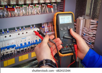 Multimeter is in hands of electrician on background of electrical automation cabinet. Adjustment of electrical control circuit for industrial equipment.