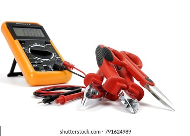 Multimeter and tools for working on a residential electrical installation, photographed on a white background.
