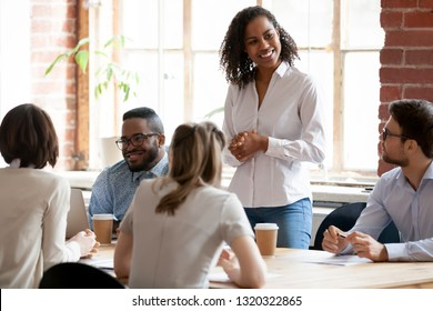 Multinational businesspeople gathered together at modern office conference boardroom partners during business meeting, black african female team leader ready to speak standing looking at colleagues