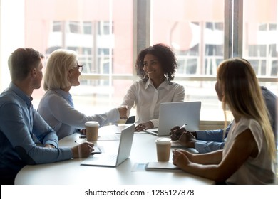 Multinational employees sitting around the table at conference room black team leader company owner shaking hands with aged confident partner people gathered at meeting for discuss further cooperation