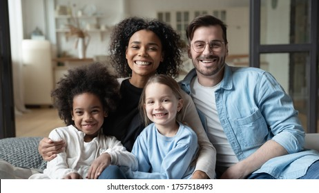 Multinational family married couple and daughters sit on couch looks at camera photo shooting feels happy. Cute multi-ethnic girls and parents portrait, homeowners, new home, prosperous future concept