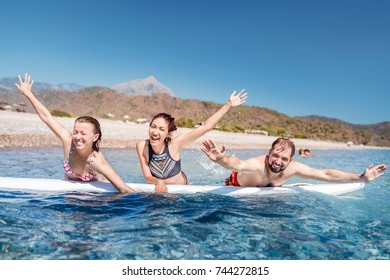 A multinational group of three friends of students laugh and swim in the sea with a board near the beach. Concept of travel and friendship