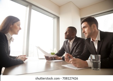 Multinational hiring managers conducting interview with caucasian young woman in formal wear. Millennial female candidate answering questions on meeting with employers, telling about work experience