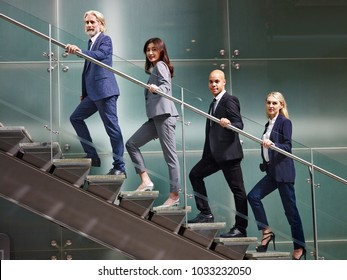 multinational and multiethnic corporate business people lined up on stairs of modern office building looking at camera smiling.