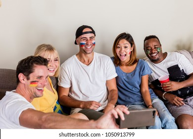 Multinational sports fans with facepainted flags laughing and taking selfie on couch
