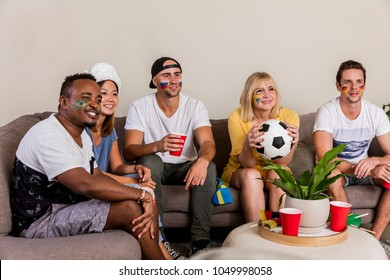 Multinational sports fans watching football on TV with cheer and excitement from couch