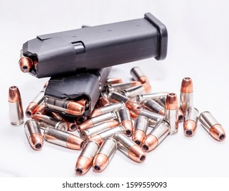 Multiple 9mm hollow point bullets with two loaded 9mm pistol magazines laying on top of them on a white background