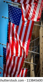 Multiple American flags blowing in the wind while hanging from buildings in New York.