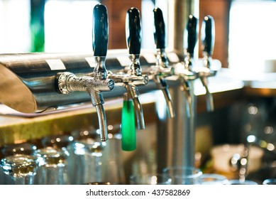 Multiple beer taps in a row. Cold and fresh beer inside.