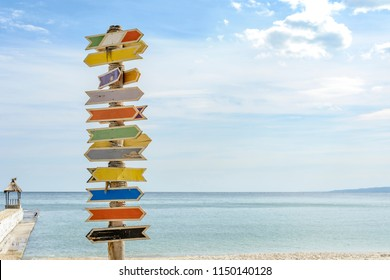 Multiple blank signs on a wooden pole in the beach.place for text