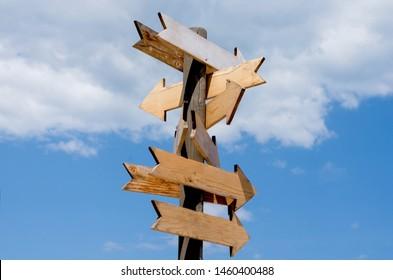 Multiple blank wooden arrow signposts on wood  pole agains blue sky  .