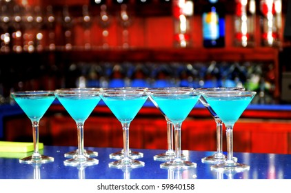 Multiple blue martinis lined up across the bar