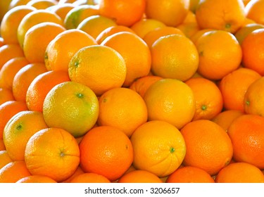 Multiple brightly colored oranges stacked on each other in daylight