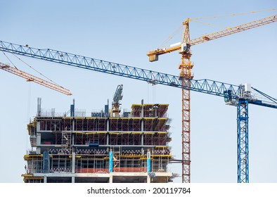 Multiple building cranes working on huge construction site