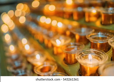 Multiple candles in the glass cups. Holiday christmas background. Religion concept wallpaper. Shallow focus. Perspective view. Vintage effect.