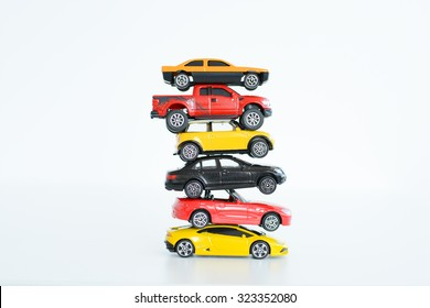 Multiple car toys on top of each other suggesting automotive industry problems