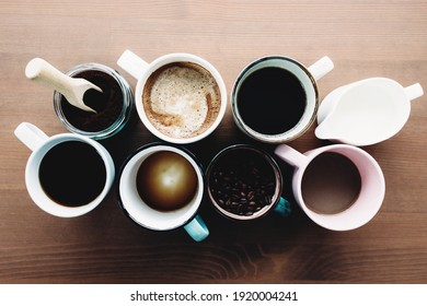 Multiple coffee cups, milk, beans and ground coffee in jar on wooden background. High quality photo