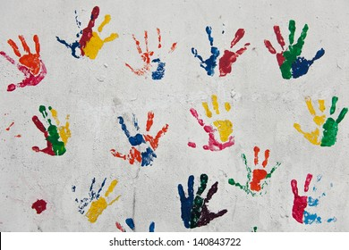 Multiple colored hand prints on white wall background.