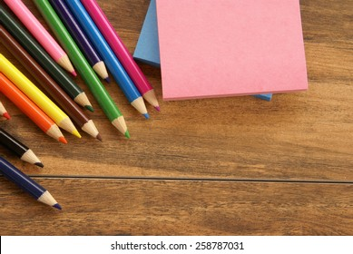 Multiple colored pencils and notepads on a wooden surface for use as a styled background.