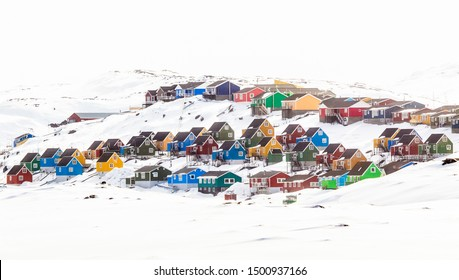 Multiple colorful Inuit houses and cottages on the hill covered in snow, Aasiaat city, Greenland