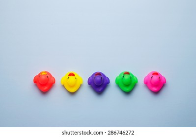 Multiple colorful rubber ducks arranged in a line pointing in a same direction over blue background, above view