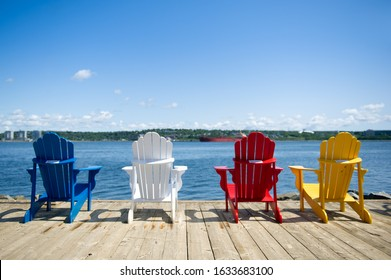 Multiple colors Adirondack chairs along the waterfront in Halifax, Nova Scotia, Canada.