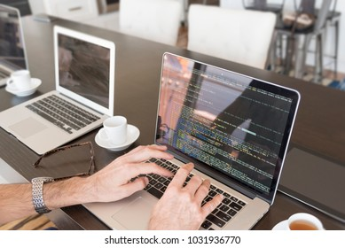 Multiple computer screens with computer code being written with hands and coffee.