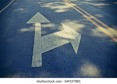 multiple direction arrows on a concrete road
