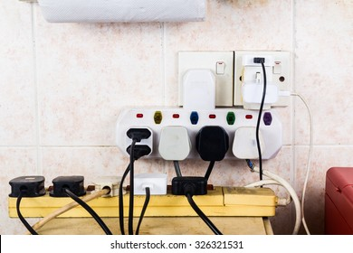 Multiple electricity plugs on adapter risk overloading and dangerous.