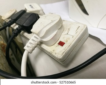 Multiple electricity plugs on adaptor risk overloading and dangerous