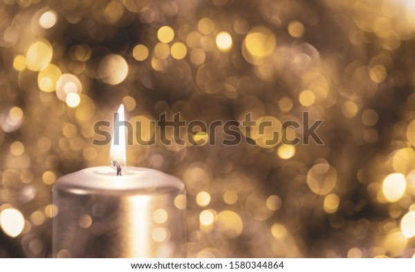 Multiple exposure of a golden Candle burning and a golden bokeh background