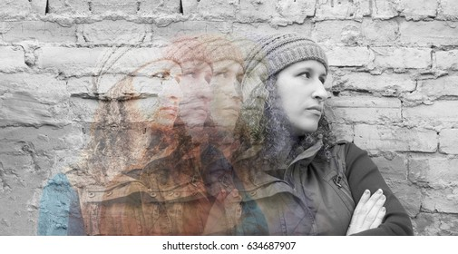 Multiple exposures of young woman standing with crossed arms against urban wall looking away, images from color fading to gray, depression and emotions concept