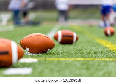 Multiple football balls are laying on a training field