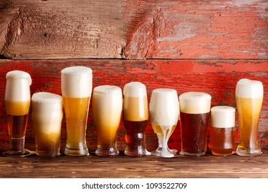 Multiple frothy lager beer pints on wooden bar bench top with a rustic timber background.