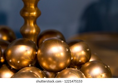 Multiple golden christmas balls in front of blue background with free room for your own text.