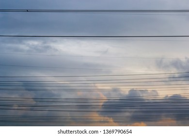 Multiple horizontal high voltage cable lines across stormy clouds, at sunset. Simple concept for power/electricity distribution and connectivity.