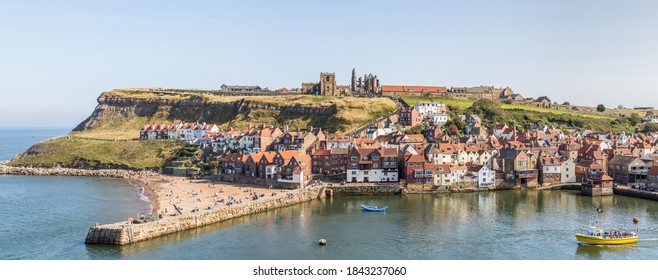 Multiple image panorama of a tourist boat exiting Whitby harbour beneath the famous Abbey and the 199 steps which lead to the hilltop.  Pictured in September 2020.