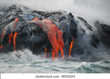 Multiple Lava Flows, Ocean, Steam, close up. Red hot lava flows through lava tubes and pours like rivers into the ocean, bringing up clouds of steam and toxic gas, adding new land to the Big Island