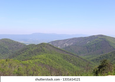 Multiple layers of mountains covered by light green vegetation; increasing level of blue in background illustrates how the mountains got their name