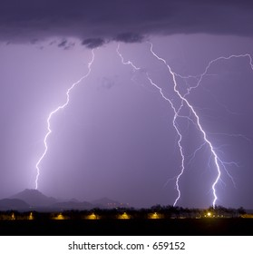 Multiple Lightning bolts and rain with airport hangers in the foreground