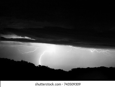Multiple Lightning Strikes from clouds to a distant hillside, lighting up the night sky.
