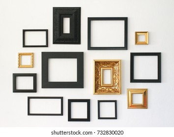 Multiple many blank small picture frames on white wall