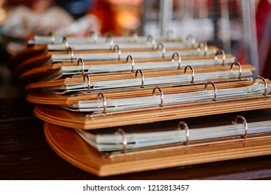 Multiple menu folders in a cafe or bar. Decorated on a wooden substrate with metal rings