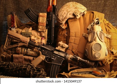 Multiple military gear items grouped together: tactical carbine, battle armor, desert camo helmet, grey gas mask, coyote backpack, rock climbing rope.