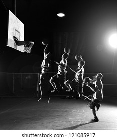 Multiple moves of a basketball player, jumping and throwing a basket at nighttime